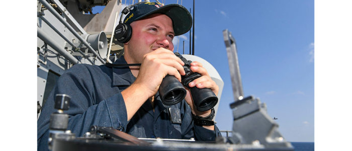 GULF OF OMAN (Feb. 9, 2020) Seaman Charles Mazer, from Mantua, New Jersey, scans the horizon for surface vessels while standing the port bridge wing lookout watch aboard the guided-missile cruiser USS Normandy (CG 60). Normandy is part of the Harry S. Truman Carrier Strike Group and is deployed to the U.S. 5th Fleet area of operations in support of naval operations to ensure maritime stability and security in the Central Region, connecting the Mediterranean and Pacific through the western Indian Ocean and three strategic choke points. (U.S. Navy photo by Mass Communication Specialist 2nd Class Michael H. Lehman)